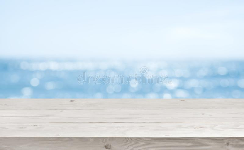 Fundo borrado do mar com primeiro plano de madeira do assoalho da plataforma do recurso foto de stock royalty free