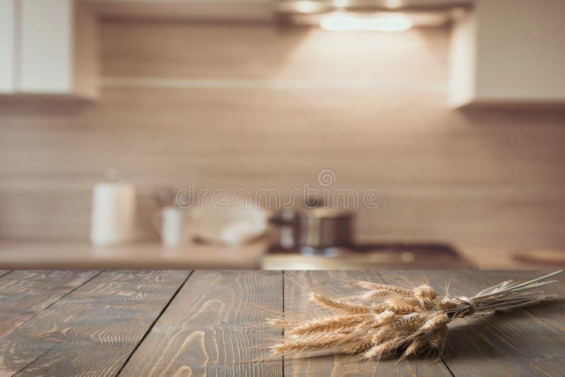 Fundo borrado e abstrato da cozinha Tabletop de madeira com trigo e cozinha moderna defocused para a exposição seus produtos imagem de stock royalty free