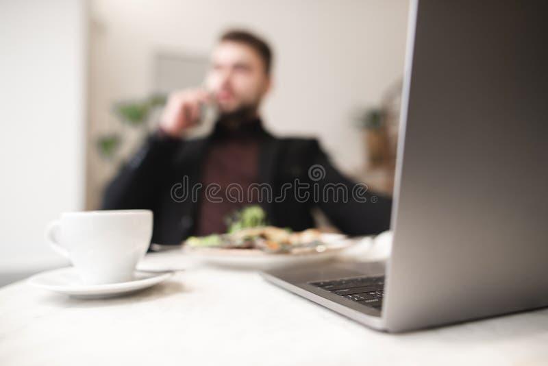 Fundo borrado O homem de negócio trabalha em um portátil, come e bebe o café Trabalho em um café fotografia de stock