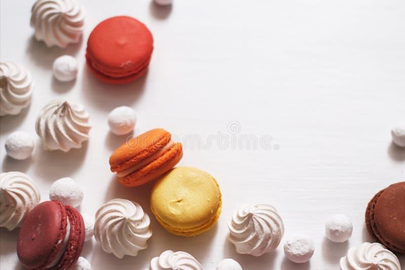 Fundo branco com merengue, bolinhos de amêndoa e arandos no açúcar fotografia de stock