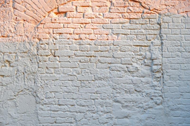Fundo branco da parede de tijolo com raios alaranjados do sol de nivelamento fotos de stock
