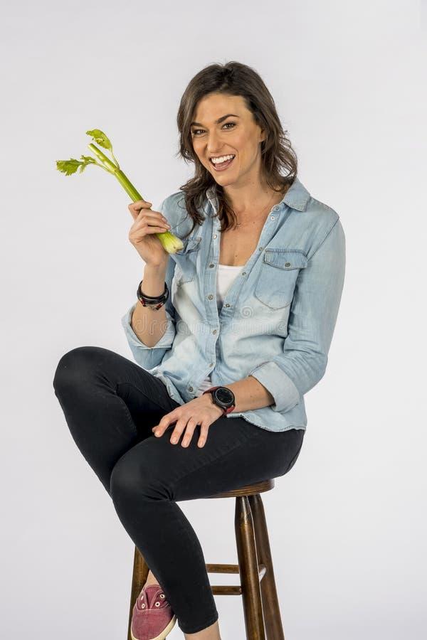 Fundo branco moreno de cabelos compridos bonito de Eating Vegetables Against A do modelo em um ambiente do estúdio fotografia de stock royalty free