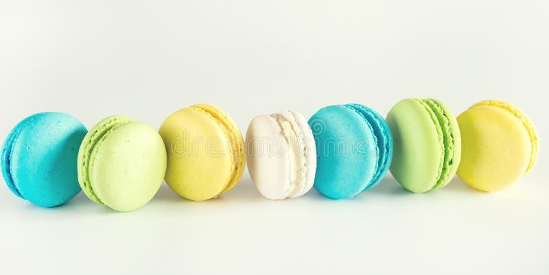 Fundo branco saboroso de Macarons da sobremesa francesa amarela colorida de Macarons do verde azul de Macarons tonificado por mui fotografia de stock royalty free