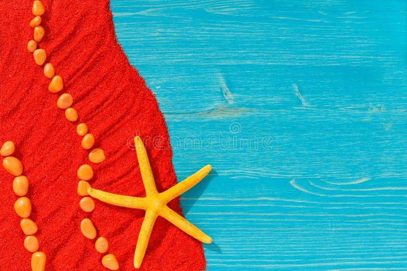 Fundo brilhante colorido com pedras alaranjadas e estrela do mar amarela na areia vermelha imagens de stock royalty free
