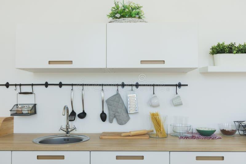 Fundo brilhante da cozinha A cozinha branca brilhante Bancadas de madeira, vista interior da cozinha minimalista elegante e AR do fotografia de stock royalty free