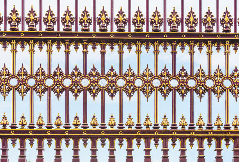 Fundo casted vermelho e dourado da cerca do ferro imagem de stock royalty free