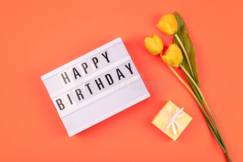 Fundo colocado liso do presente do feliz aniversario da celebração Caixa leve com feliz aniversario do texto e ramalhete de tulip fotografia de stock