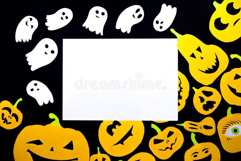 Fundo colorido de grupos de abóboras cortadas de papel laranja e de fantasmas de papel branco isolado em preto imagens de stock