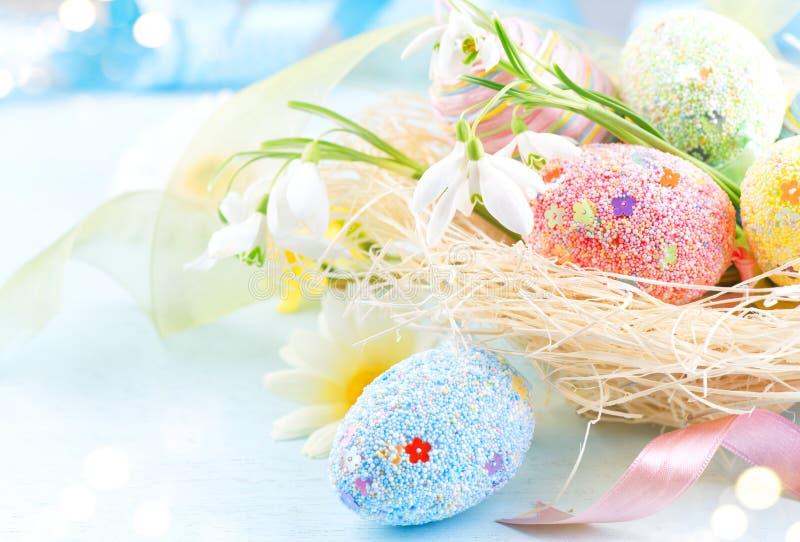 Fundo colorido dos ovos da Páscoa Ovos coloridos bonitos com as decorações sobre o fundo de madeira azul, projeto da beira foto de stock