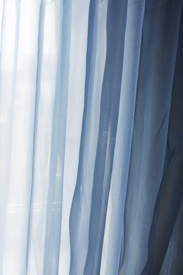 Fundo com as cortinas azuis de matéria têxtil fotografia de stock