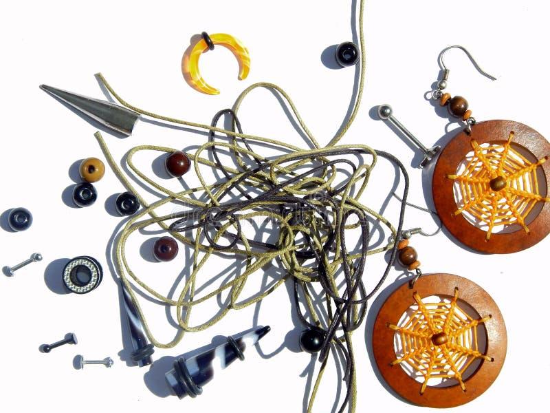 Fundo com brincos piercing, brincos alaranjados, grânulos, cordas para braceletes imagens de stock