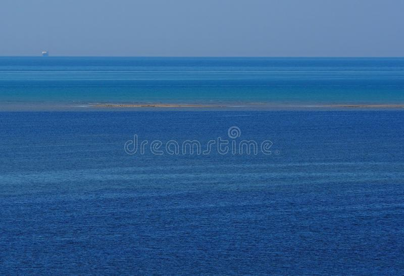 Fundo com máscaras diferentes do azul, uma listra do Seascape de uma ilha arenosa emersa pequena no navio médio e distante fotos de stock
