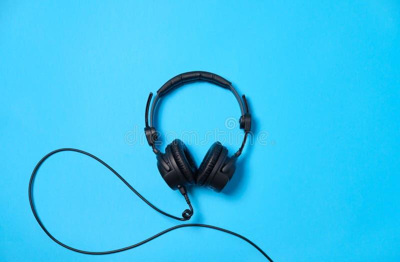 Fundo com os fones de ouvido na tabela azul, configuração lisa da música ou do podcast Vista superior, configuração lisa, espaço  fotografia de stock royalty free