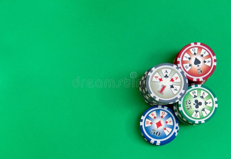 Fundo com a pilha das microplaquetas de pôquer na tabela verde fotos de stock