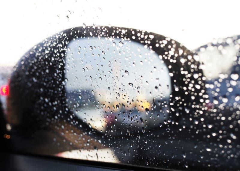 Fundo com um espelho de carro com gotas da chuva foto de stock