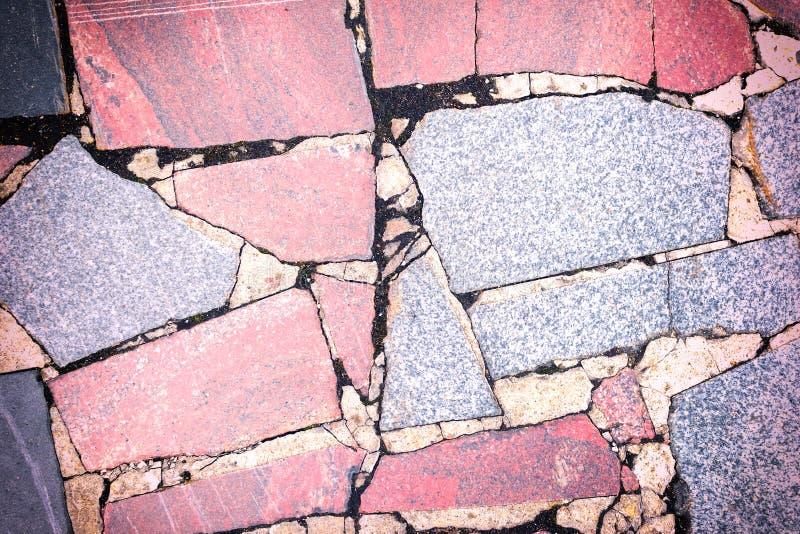 Fundo com uma textura de um mosaico de pedra Os grandes fragmentos vermelhos e cinzentos do granito são apresentados caoticamente foto de stock