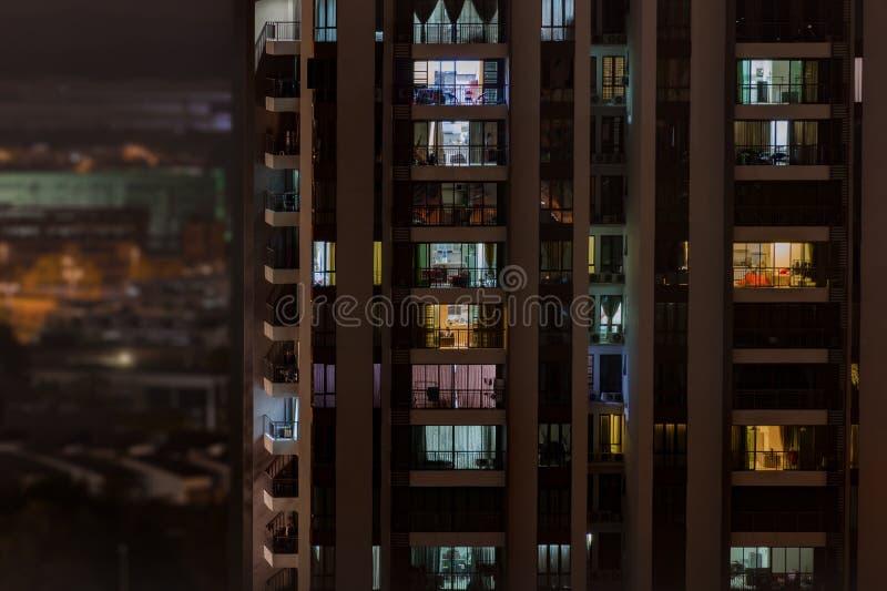 Fundo com vida noturna na cidade grande - prédio moderno com as janelas dos apartamentos acolhedores em que a luz brilha imagens de stock
