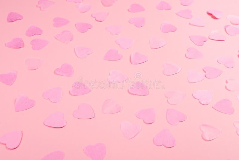 Fundo cor-de-rosa com confetes coração-dados forma imagem de stock