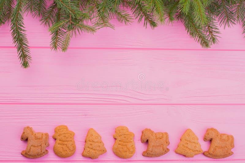 Fundo cor-de-rosa com ramos do abeto vermelho e cookies do pão-de-espécie imagens de stock royalty free