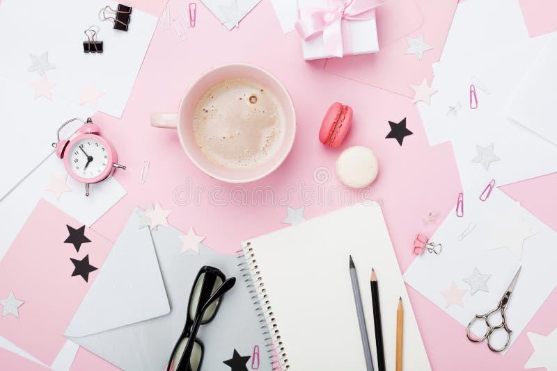 Fundo cor-de-rosa do local de trabalho da mulher da forma Café, macaron, material de escritório, presente e caderno limpo na opin imagens de stock royalty free