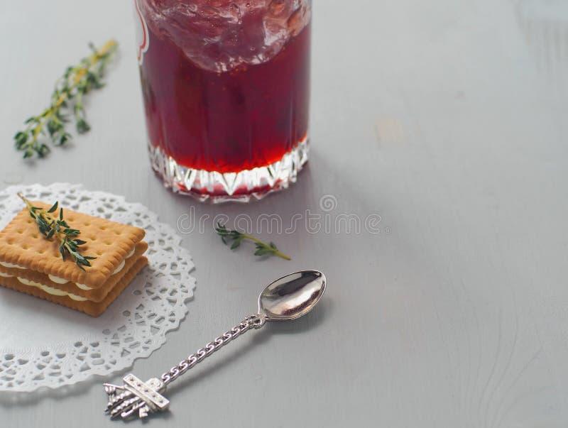 Fundo culinário Cookie mergulhada decorada com os ramos frescos do tomilho e um vidro do doce de morango meio cheio com colher en imagens de stock royalty free