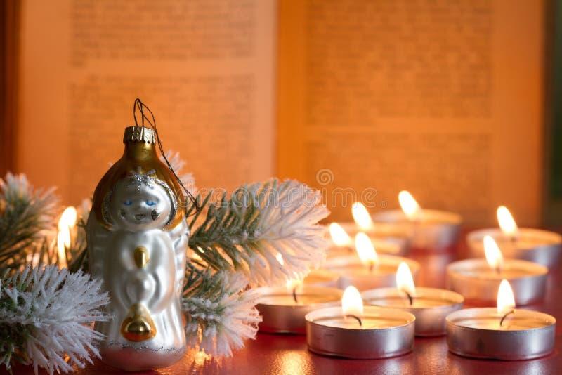 Fundo da Bíblia da árvore da quinquilharia e do Natal do sumário da vela na noite imagem de stock