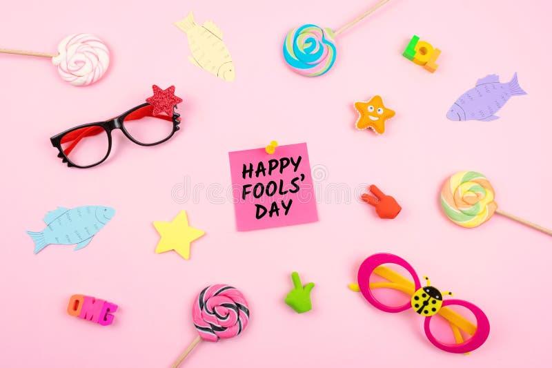 Fundo da celebração do dia de April Fools 'com peixes de papel, nota pegajosa e decoração no fundo cor-de-rosa Tudo engana 'o dia fotografia de stock royalty free