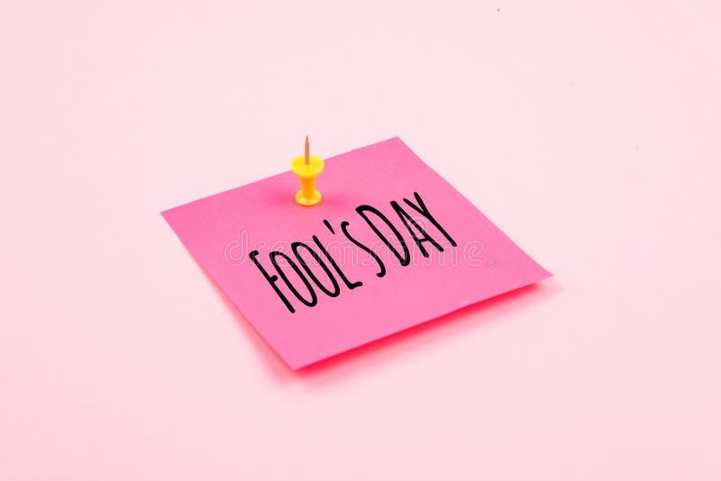 Fundo da celebração do texto do dia de April Fools 'com o pino pegajoso de papel da nota e do escritório no fundo cor-de-rosa Tud imagem de stock
