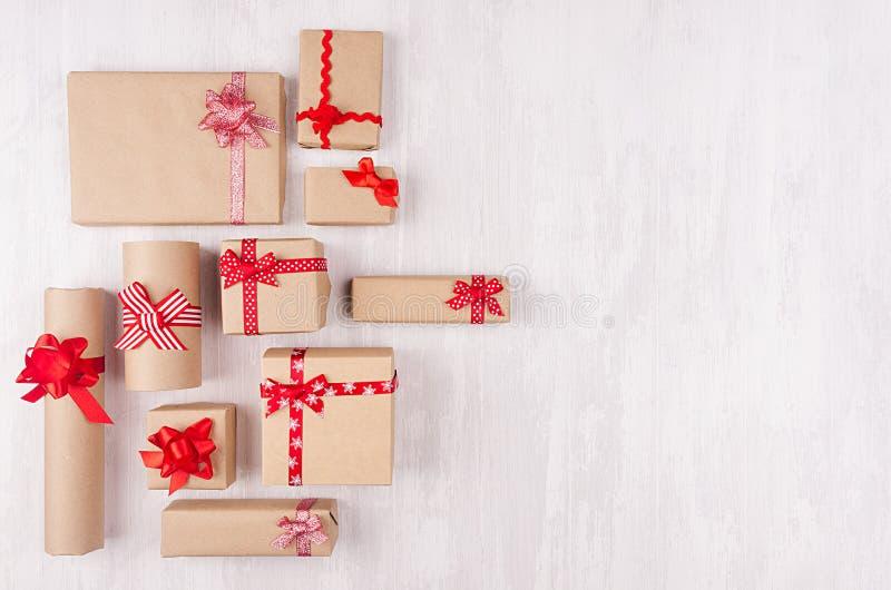 Fundo da celebração do ano novo - presentes de papel do ofício amável diferente com fitas e curvas vermelhas na prancha de madeir foto de stock royalty free