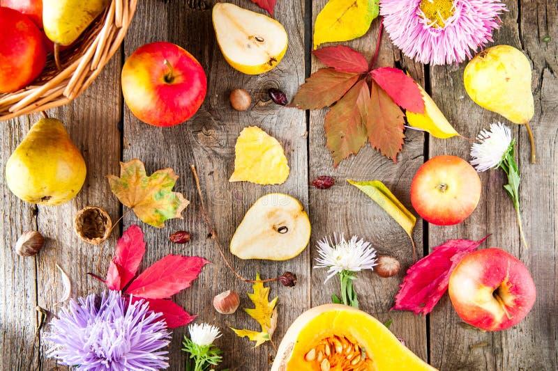 Fundo da colheita ou da ação de graças com frutos, as flores, as folhas, a abóbora, as porcas e as bagas outonais na tabela de ma foto de stock