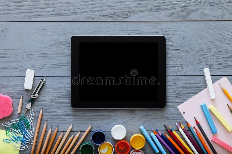 Fundo da escola, fontes do estudo da criança e zombaria digital da tabuleta acima da tela no fundo de madeira cinzento cinzento,  imagens de stock