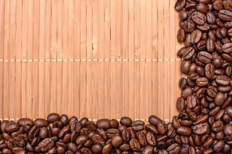 Fundo da esteira de bambu polvilhado em torno das bordas do café fritado das grões, espaço para o texto imagens de stock royalty free