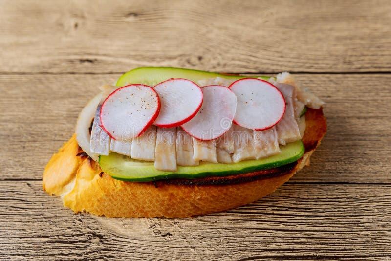 fundo da madeira dos arenques do sanduíche do rabanete da cebola do pepino imagens de stock royalty free