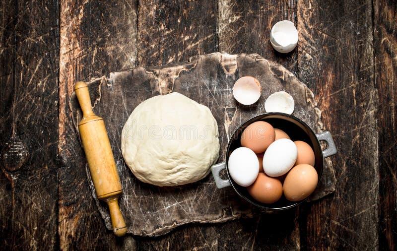 Fundo da massa A massa com um pino do rolo e uns ovos frescos na placa de madeira velha foto de stock royalty free