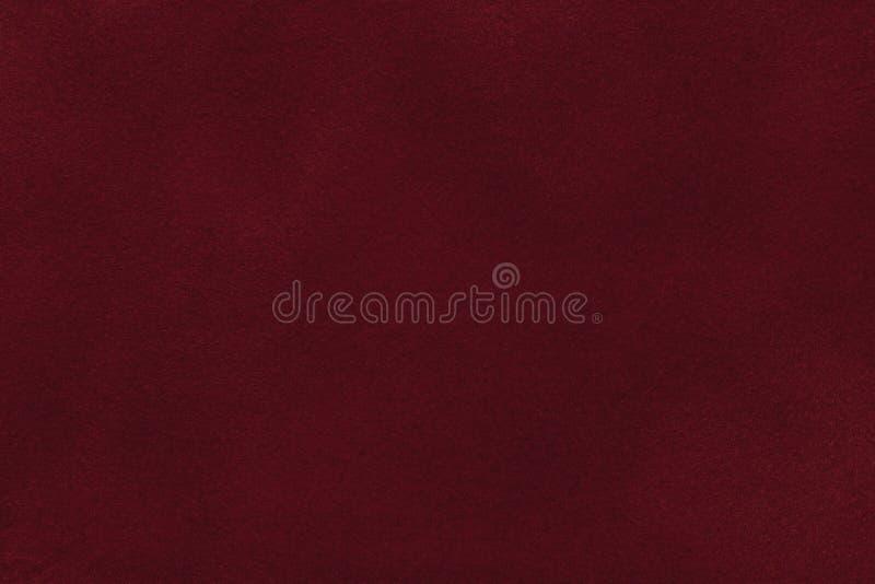 Fundo da obscuridade - close up vermelho da tela da camurça Textura matt de veludo da matéria têxtil do nubuck do vinho imagem de stock royalty free