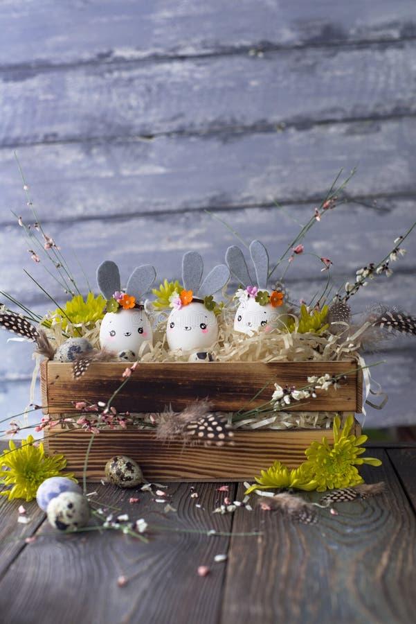 Fundo da Páscoa, coelhos caseiros da casca de ovo e crisântemo amarelo na caixa de madeira fotos de stock royalty free