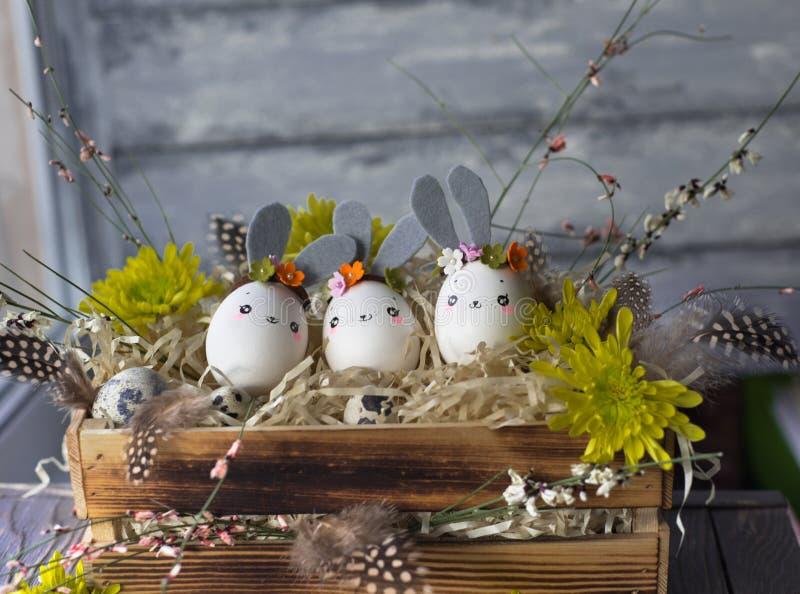 Fundo da Páscoa, coelhos caseiros da casca de ovo e crisântemo amarelo na caixa de madeira imagens de stock royalty free