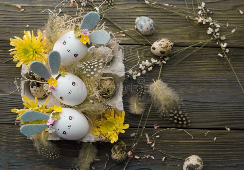 Fundo da Páscoa, coelhos caseiros das cascas de ovo e crisântemo amarelo em umas caixas de cartão fotografia de stock
