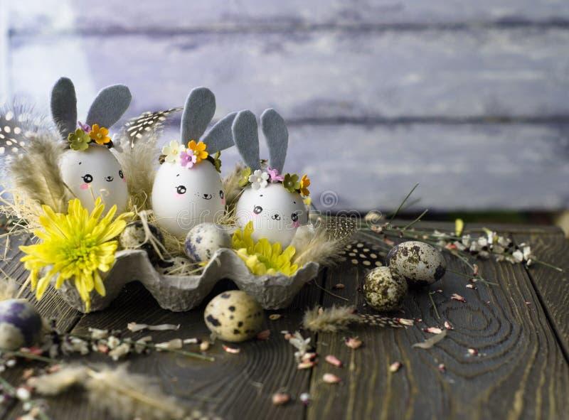 Fundo da Páscoa, coelhos caseiros das cascas de ovo e crisântemo amarelo em umas caixas de cartão imagem de stock