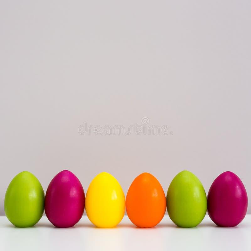 Fundo da Páscoa - fim acima de ovos da páscoa e do espaço pintados coloridos da cópia sobre a parede imagens de stock royalty free
