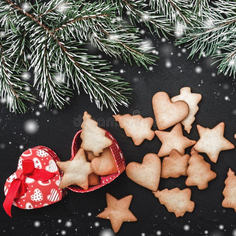 Fundo da pedra do quadrado preto com ramos do abeto Efeito da neve Uma caixa coração-dada forma dos biscoitos de várias formas imagem de stock royalty free