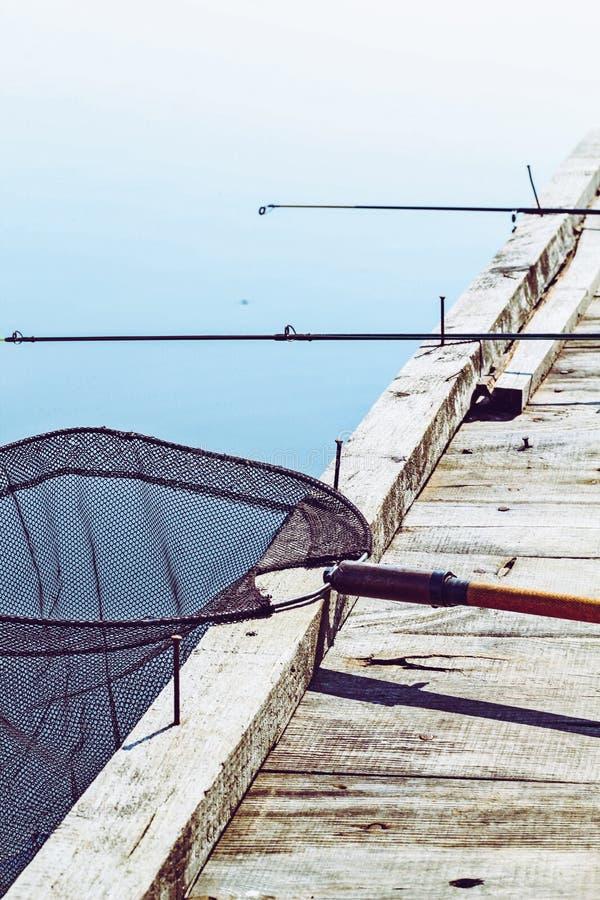 Fundo da pesca Imagem tonificada retro do equipamento de pesca no cais de madeira Pescando a plataforma no lago fotos de stock royalty free