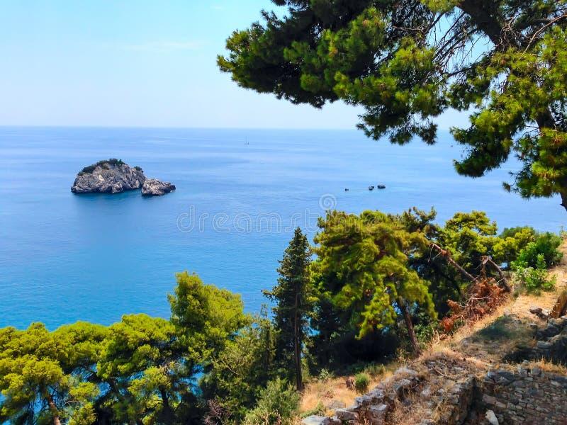 Fundo das férias de verão com a baía da água do mar de turquesa, nountains, pinheiros foto de stock royalty free