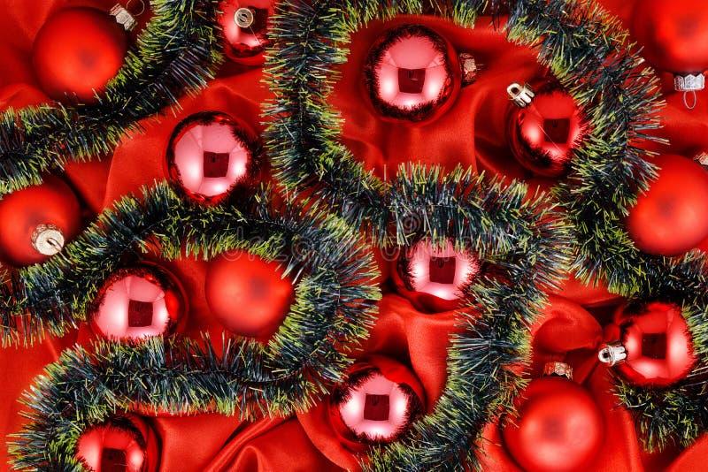 Fundo de bolas vermelhas da árvore de Natal com ouro e de decorações verdes na tela de seda vermelha imagem de stock royalty free