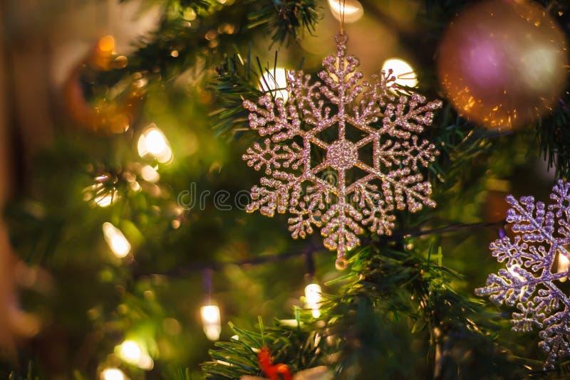 Fundo de brilho de prata festivo de suspens?o da quinquilharia do floco de neve com a ?rvore de Natal verde decorada no shopping  fotos de stock