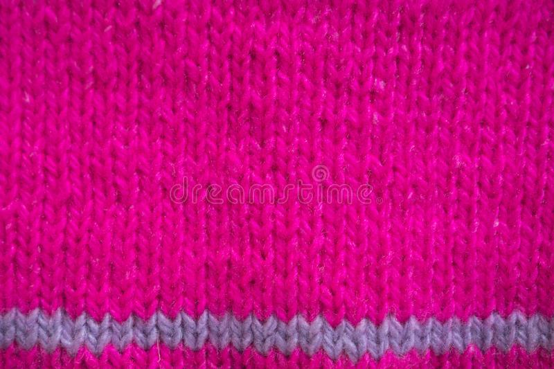 Fundo de inverno com textura horizontal Fragmento de cor rosa forte ligado às agulhas do suor para crianças fotografia de stock royalty free