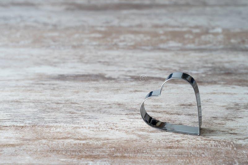 Fundo de madeira acolhedor, com um molde coração-dado forma da cozinha na parte inferior, conceito do amor, para o dia de Valenti fotografia de stock