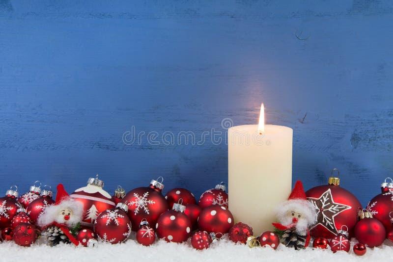 Fundo de madeira azul do Natal com uma vela branca e um bal vermelho fotografia de stock royalty free