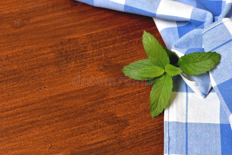 Fundo de madeira borrado rústico com a toalha e a hortelã azuis de cozinha fotografia de stock