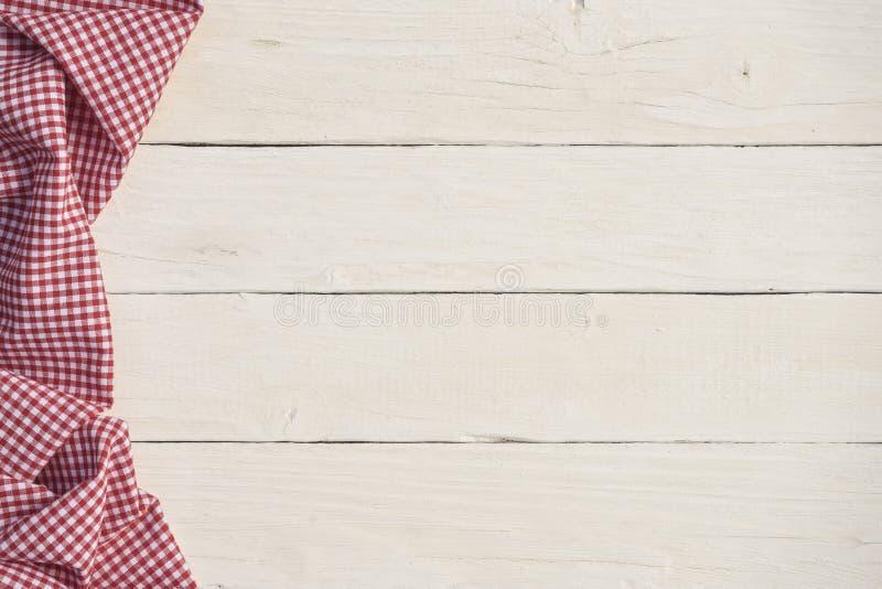 Fundo de madeira branco com uma toalha de mesa quadriculado vermelha imagem de stock royalty free
